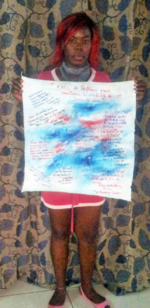 Edinedi d'AFTA Togo tenant la toile confectionnée par les participantes pour les partenaires. (Photo par Erin Royal Brokovitch)